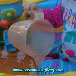 toddler using a plastic jug to pour water in a paddling pool
