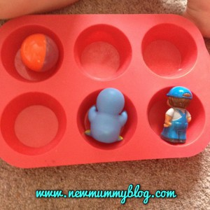 toddler using a muffin tray for sorting