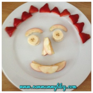 a face made from apple segments, bananas and strawberries