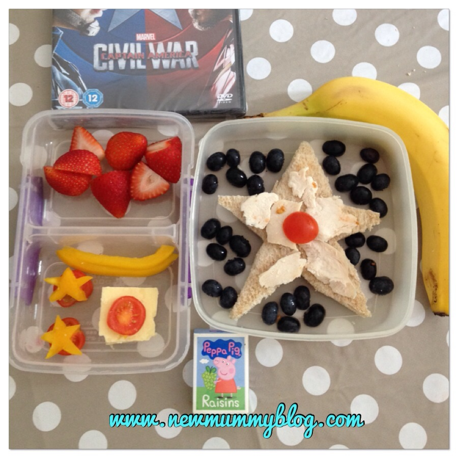 captain america DVD theme healthy lunch blueberries surround a star sandwich with a side of strawberries, pepper stars on tomatoes, with a banana and raisins.