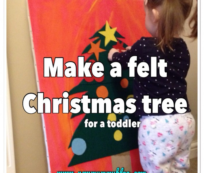toddler playing with a homemade felt christmas tree