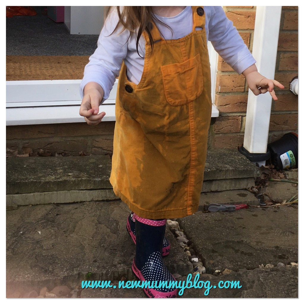 Toddler soaked by water following outdoor play - sailing duck across the wheel barrow, yellow pinafore. New mummy blog