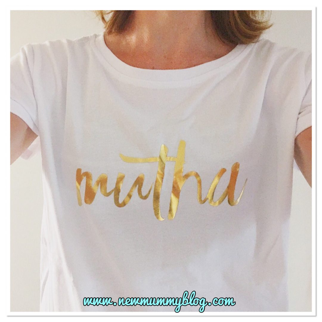 Wearing a white Milky Tee Company breastfeeding t-shirt which has Mutha written in gold letters, with long zips on the sides